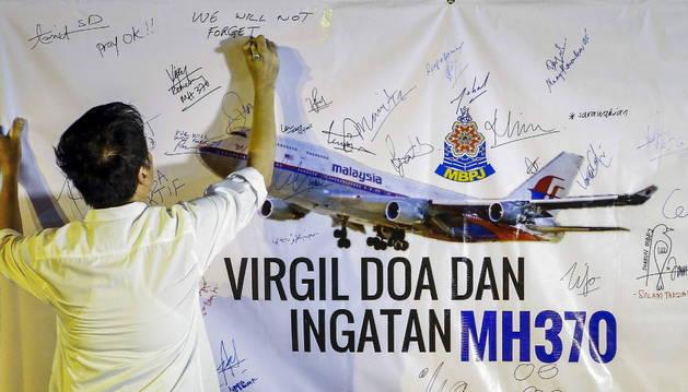 Un hombre escribe un mensaje en recuerdo de las víctimas del vuelo