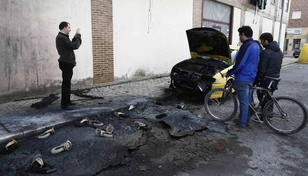 Varias personas miran el estado en el que ha quedado un vehículo y la fachada de un edificio donde varios contenedores han sido quemados esta madrugada