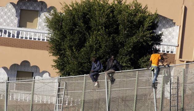 Tres inmigrantes, encaramados en la valla seis horas después del intento.