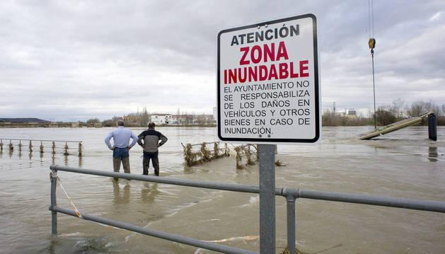 Dos personas, en el embarcadero destrozado por la crecida del río Ebro en Tudela.