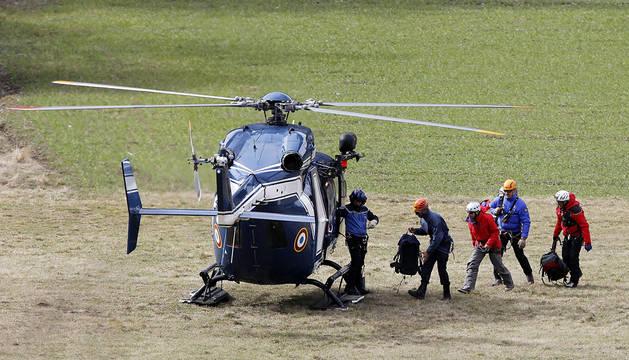 Miembros de los equipos de rescaten suben a un helicóptero en la base de operaciones en Seyne-les-Alpes.