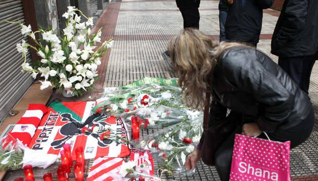Una mujer deposita una flor en el lugar en el que murió Íñigo Cabacas