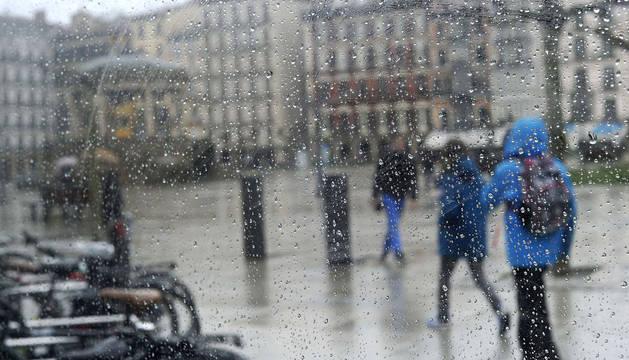 Varias personas, caminando bajo la lluvia en Pamplona esta semana.