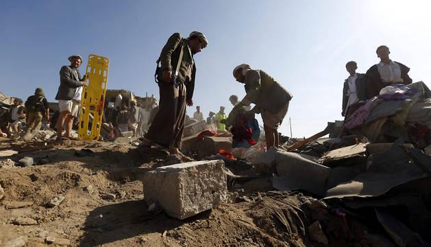 Miembros armados de las milicias hutíes inspeccionan el lugar donde se ha producido un bombardeo saudí en un barrio en Saná.