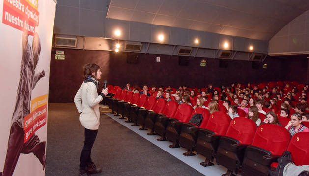 Una responsable del programa se dirige a los escolares en la sala de cine.