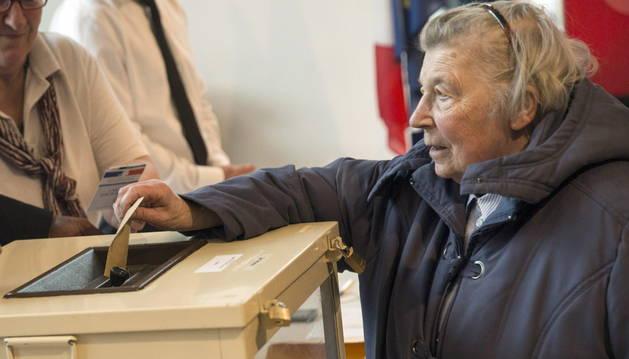 Una mujer deposita su voto en Francia.