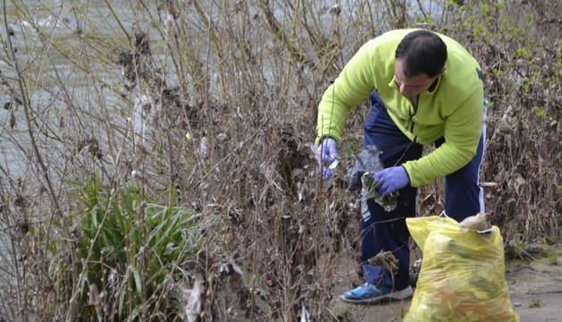 Un voluntario quita plásticos de las ramas en la zona de Los Llanos.