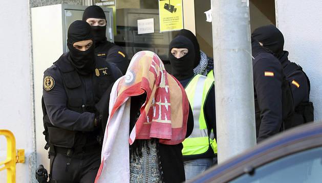 Agentes de la Guardia Civil escoltan a la mujer que, junto a su marido y a sus dos hijos gemelos, han sido detenidos esta madrugada en Badalona (Barcelona).