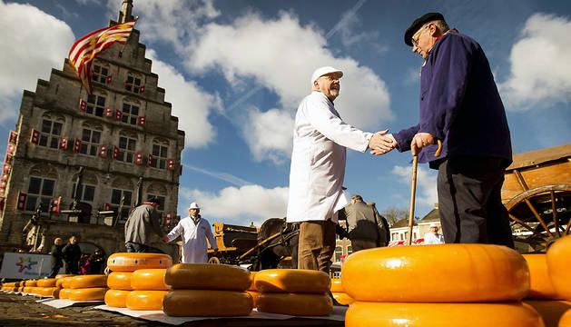 Un inspector (izda) y un vendedor negocian el precio de un queso.
