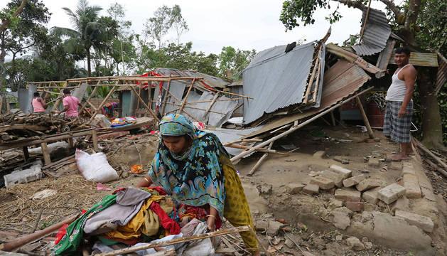 Una mujer recoge los restos de su casa destrozada.