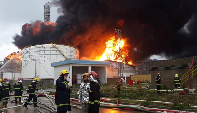 Varios bomberos, junto a la planta en llamas en Zhangzhou.