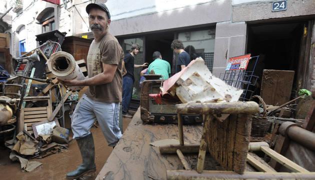 Un hombre retira material deteriorado en las inundaciones registradas en julio en Elizondo.