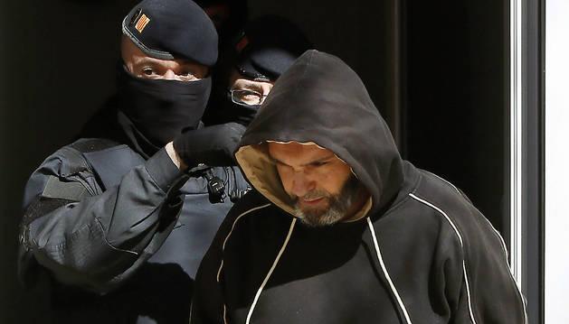 Agentes de los Mossos d'Esquadra custodian a una de las nueve personas arrestadas este miércoles.