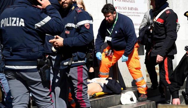 Policías y miembros de los servicios de rescate asisten a un herido a las puertas del Palacio de Justicia en Milán.
