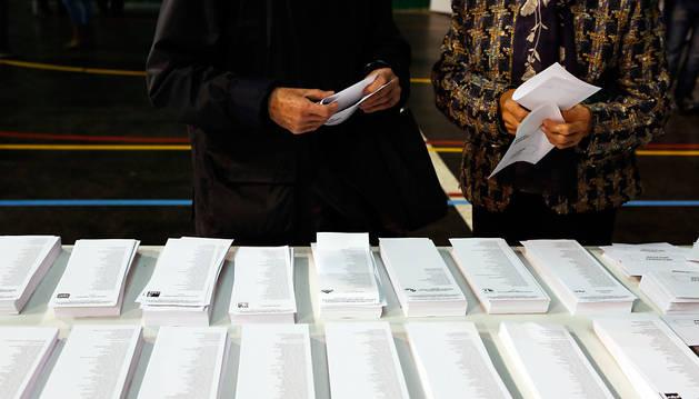 Dos ciudadanos seleccionan la papeleta de votación.
