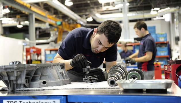El operario de una fábrica ajusta varios engranajes.