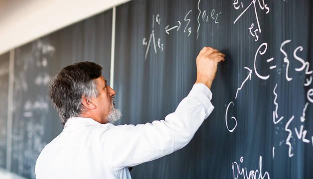 Un profesor escribe en la pizarra.