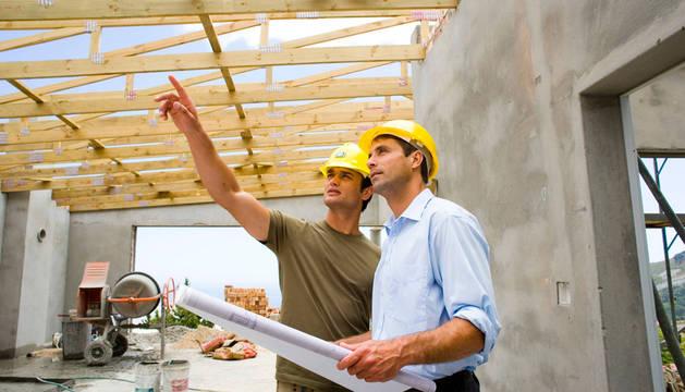 Dos personas revisan los planos de una obra.