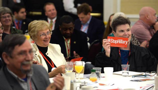 Un  mujer porta un cartel en contra de Clinton en el encuentro republicano en Nuevo Hampshire.