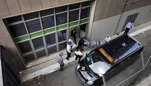Miembros de los servicios funerarios de Barcelona y del juzgado de guardia retiran el cadáver del profesor.