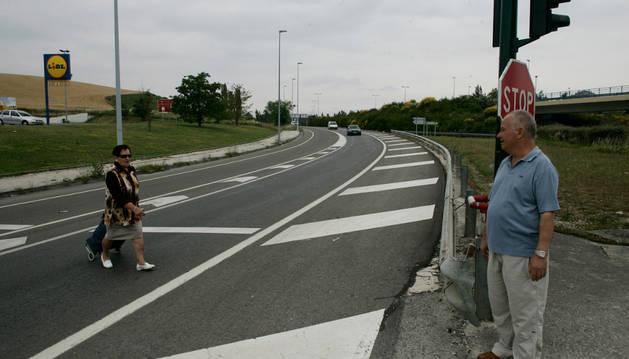 Dos personas cruzan la carretera en un punto en el que no hay paso de peatones.