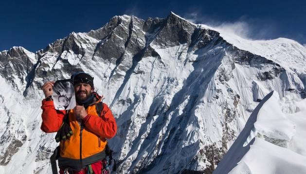 Javier Camacho sostiene una foto de su mujer y su hijo en la cima de Island Peak. Tras él, el Lhotse