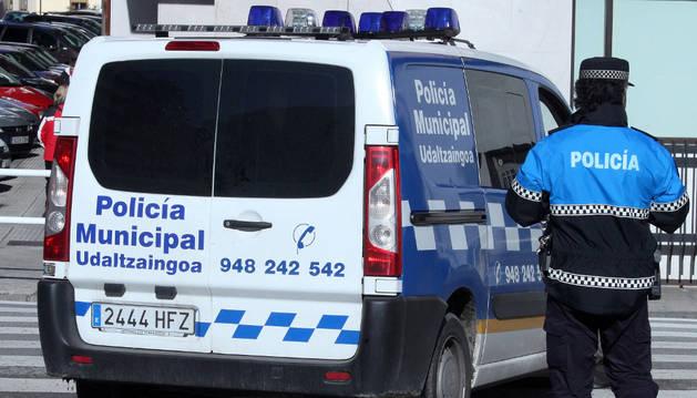 Un agente junto a un vehículo policial en Burlada.
