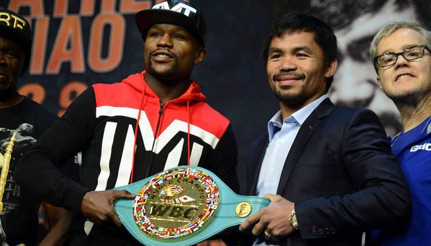 Manny Pacquiao y Floyd Mayweather sostienen el cinturón esmeralda.