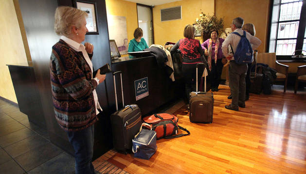 Varios turistas con sus maletas, en la recepción de un hotel de Tudela.