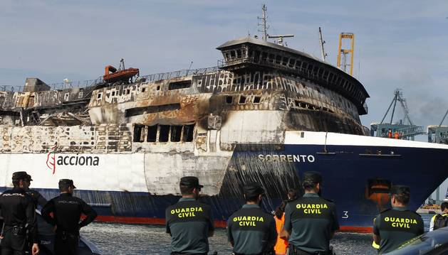 Miembros de la Guardia Civil y la Policía Nacional observan la llegada del Sorrento a Sagunto.