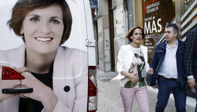 La candidata del PSN a la Presidencia de Navarra, María Chivite, y el secretario de organización del partido, Santos Cerdán, pasan junto a un vehiculo electoral.