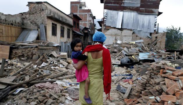 Una mujer y su hija caminan sobre escombros en la localidad de Sankhu, Nepal.