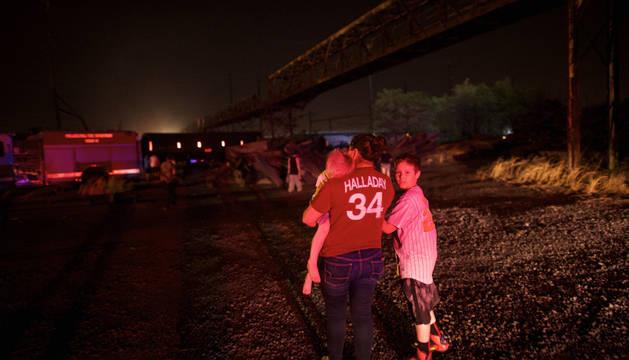 Una mujer y su hijo observan el tren descarrilado.