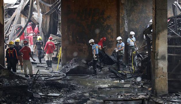 Equipos de rescate en la fábrica de zapatos afectada por el fuego.