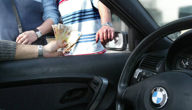 Un hombre muestra a otros varios billetes.