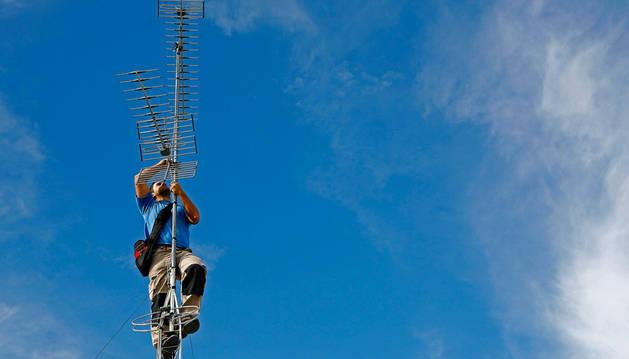 Un antenista trabaja en la instalación de un tejado.