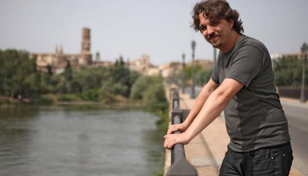 Daniel López Córdoba posa en el puente del Ebro con la torre de la catedral al fondo de la imagen.