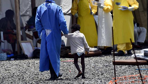 Una enfermera lleva a un niño con ébola al hospital.