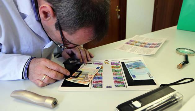 Un técnico del laboratorio criminalístico de la Guardia Civil verifica la autenticidad de varios billetes con una lupa de aumento.