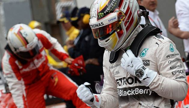 Hamilton celebra su primera posición en la calificación, con Vettel al fondo.