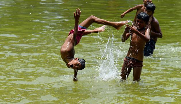 Varios niños se bañan en Nueva Delhi.