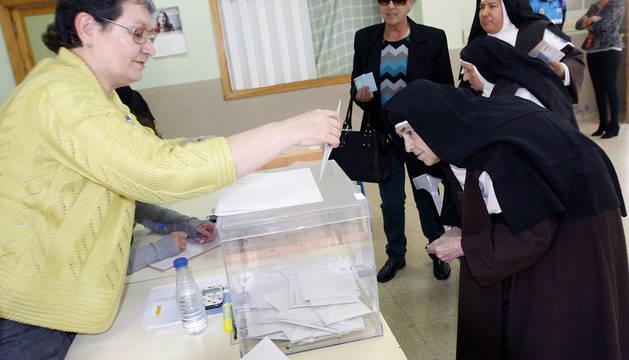 Una monja de clausura del convento de Santa Clara observa la urna mientras ejerce su derecho al voto en un colegio electoral de Ciudad Rodrigo.