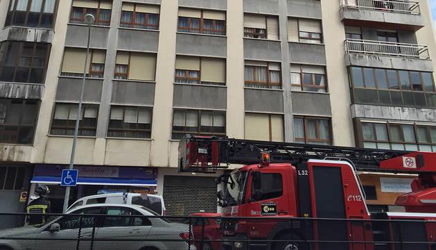 Los bomberos, frente a la vivienda en la que se ha producido el incendio.