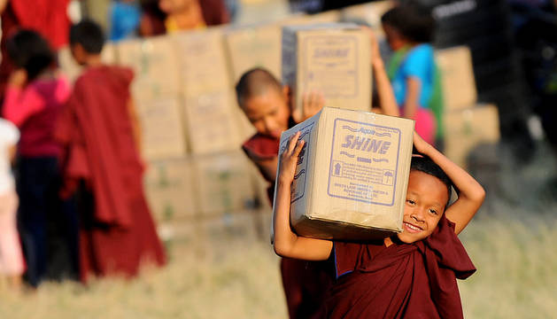 Niños budistas transportan alimentos en Kathmandu.