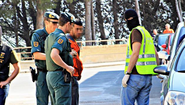 Agentes de la Guardia Civil custodian al vecino de Ribaforada durante el arresto.