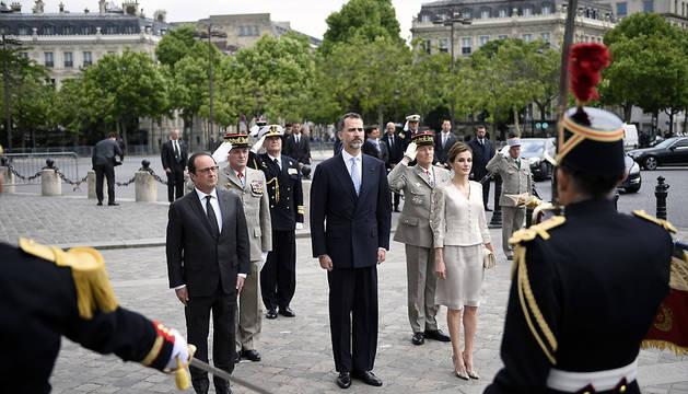 François Hollande y los Reyes escuchan los himnos nacionales junto al Arco del Triunfo.
