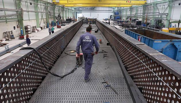 Un trabajador camina por el interior de la pasarela de acero.