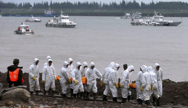 Varios miembros de los servicios de rescate transportan los cadáveres de dos víctimas a orillas del río Yangtsé.
