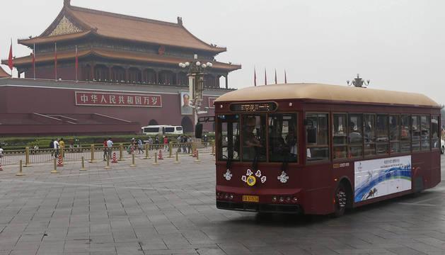 Un autobús turístico atraviesa la plaza de Tiananmén.