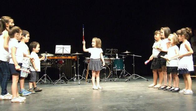 Una niña 'dirige' a sus compañeros durante una de las actuaciones del concierto.